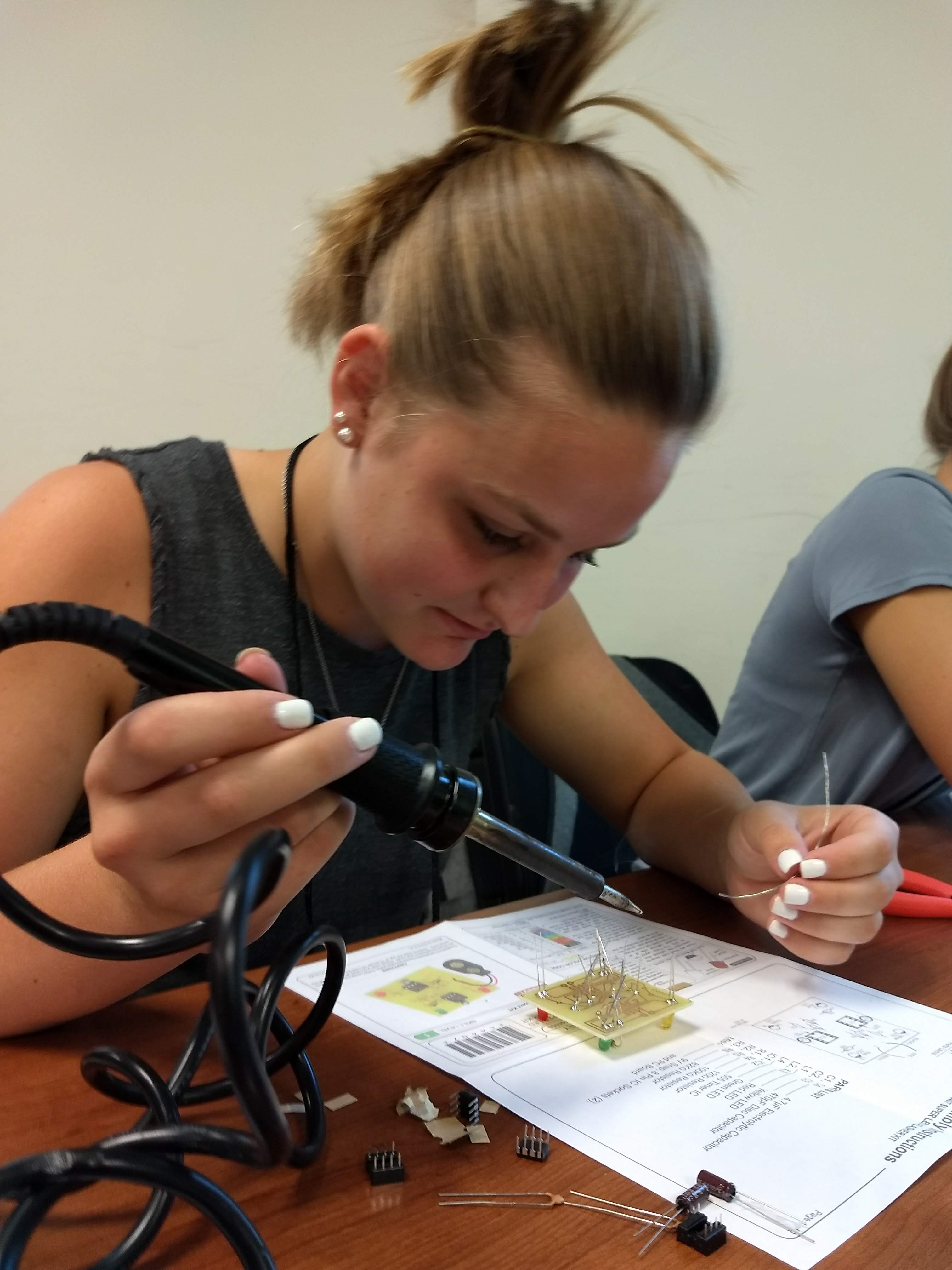 Grace Henderson soldering on her circuit board during one of the workshops at 4-H Electric Congress