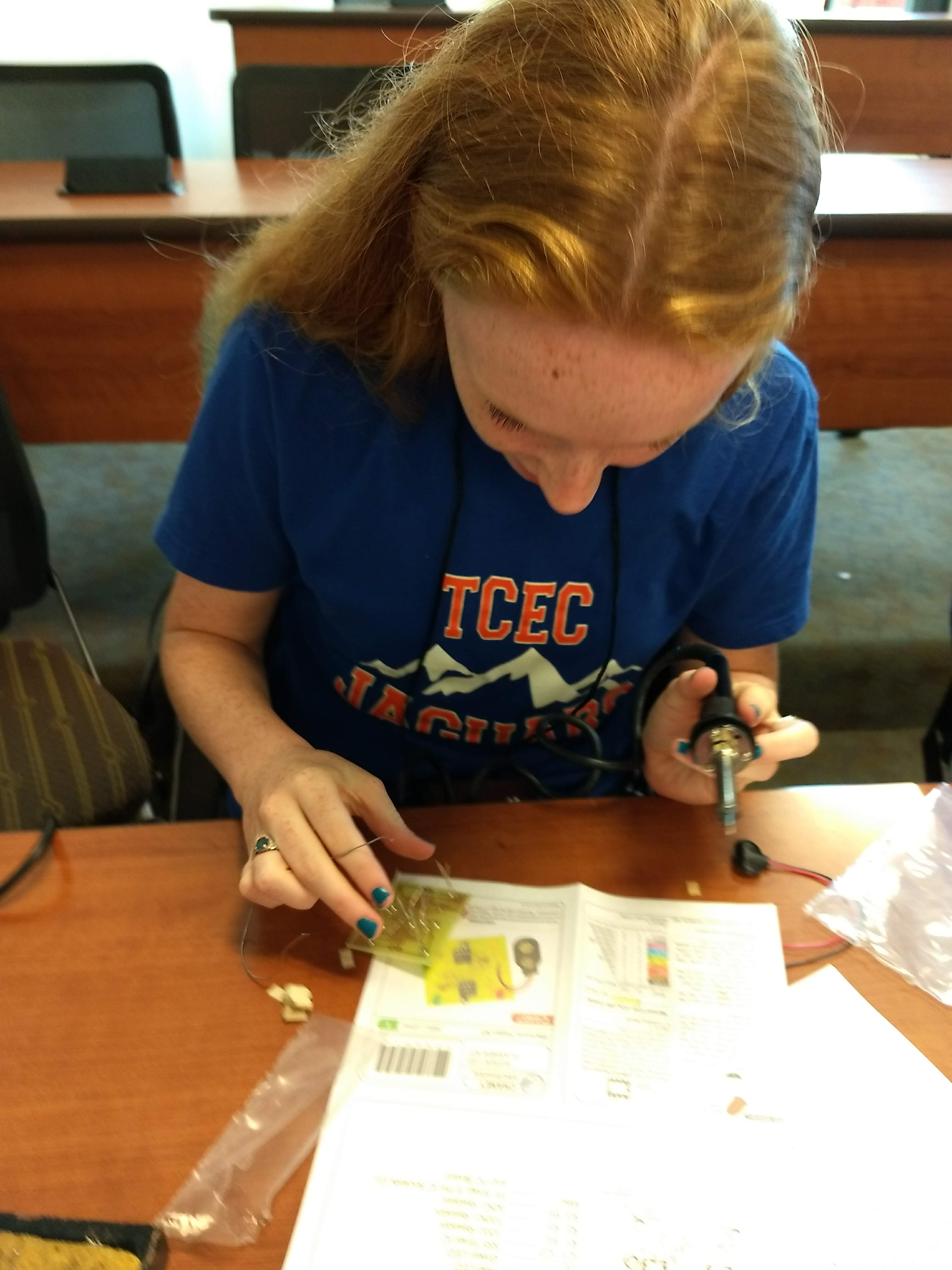 Hannah Smith studying her circuit board making sure everything is right before she solders